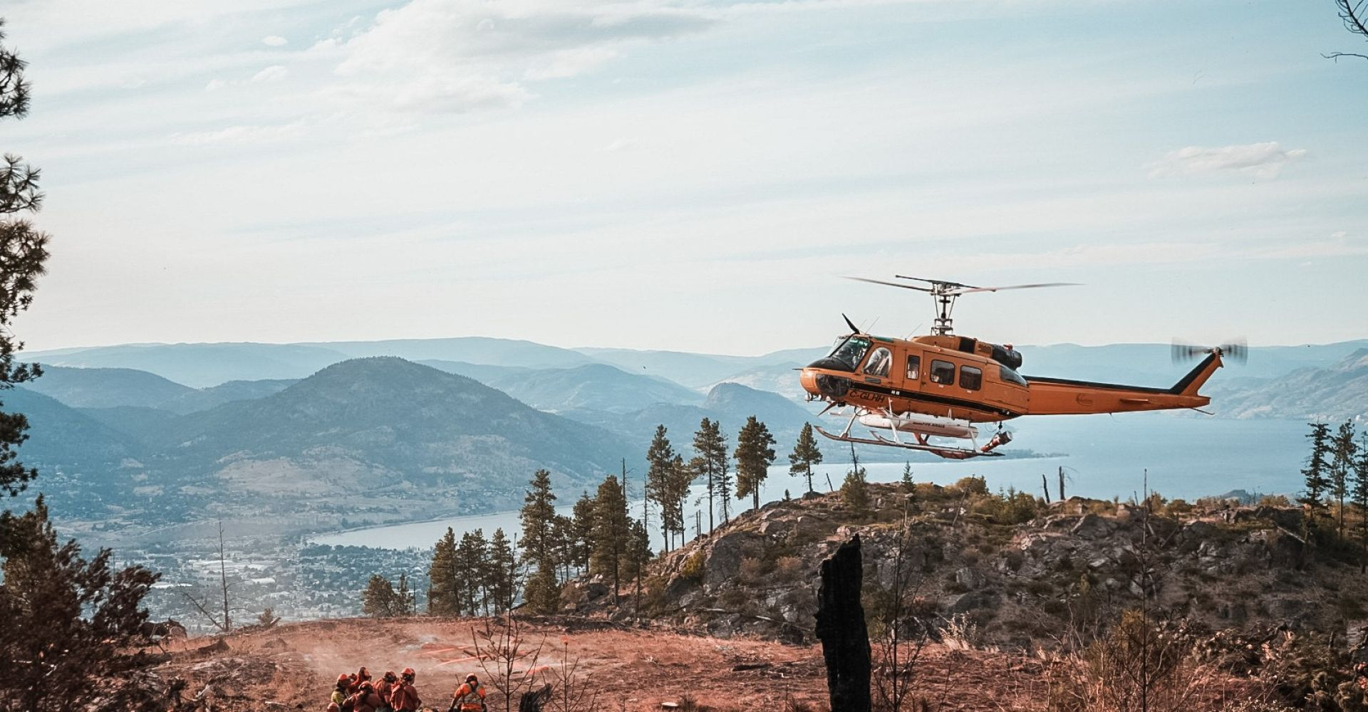 Fire Helicoptor landing on top of mountain with fire crews below