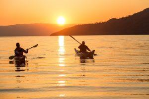 couple kayaking on lake with sunset behind