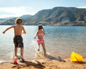 A family enjoys a beach day at Skaha Lake in Penticton, BC.
