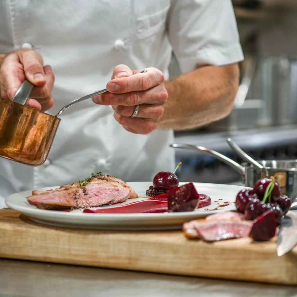 a chef preparing plate at Naramata Inn