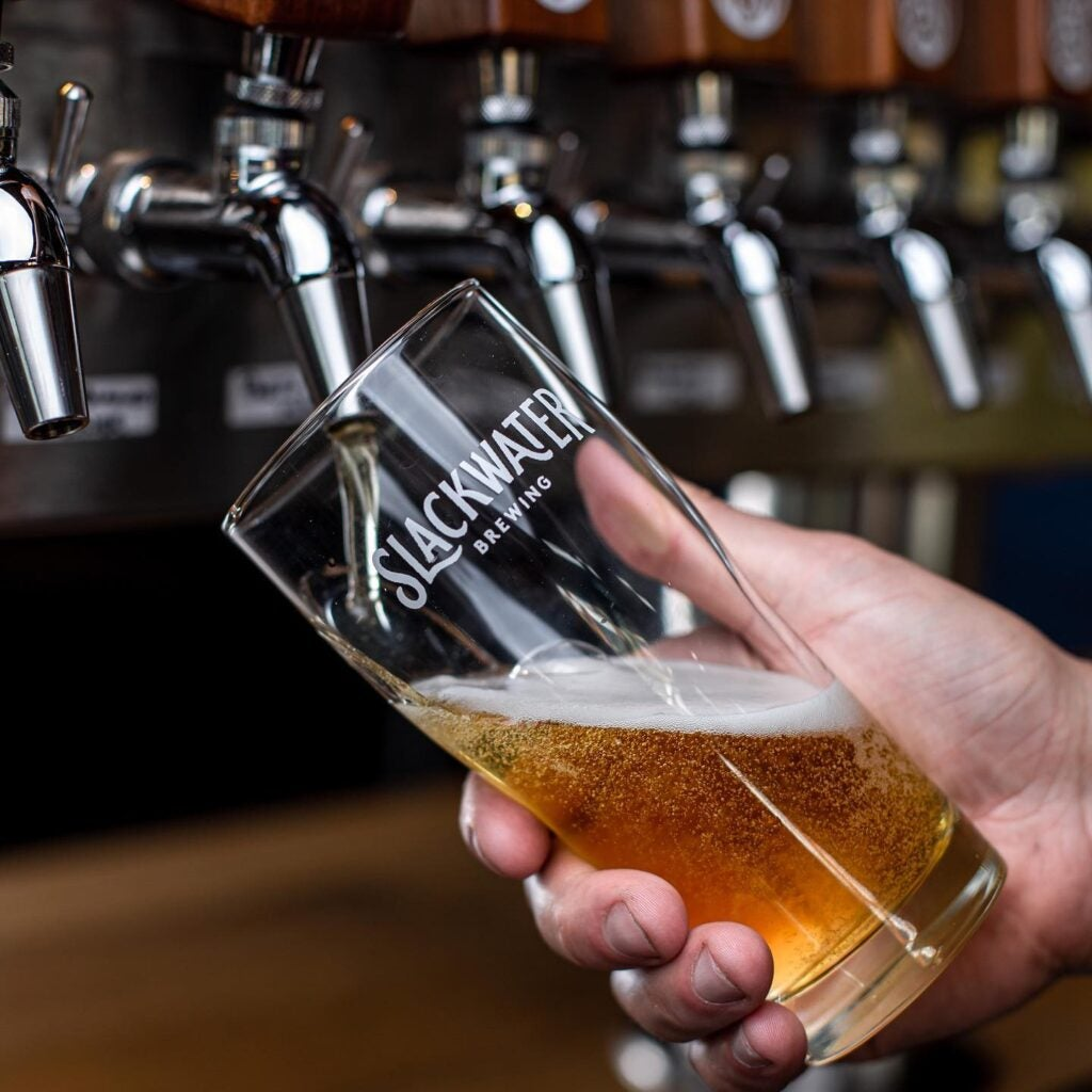 Slackwater beer being poured in a Slackwater glass