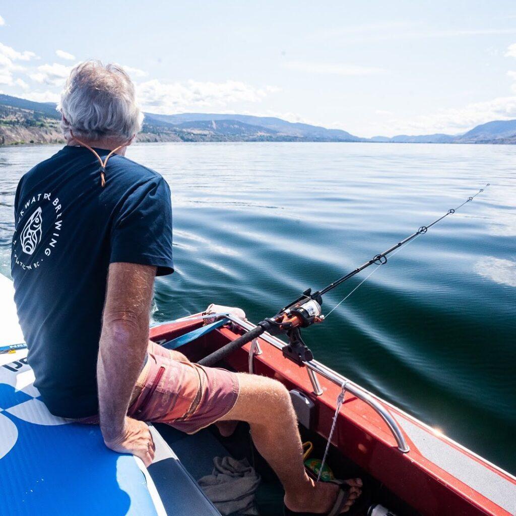 man fishing on Okanagan Lake with a Slackwater t-shirt on