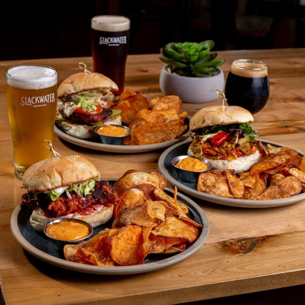 Three plates of food and beers at Slackwater Brewing